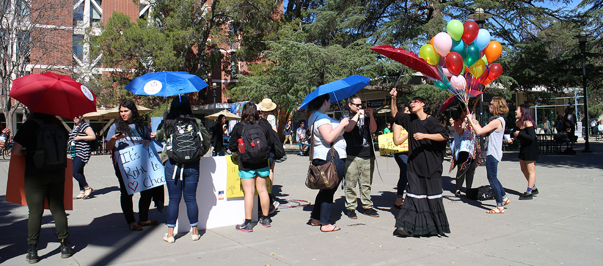 Pro-choice protesters at UC Davis in a line in front of our poll table.