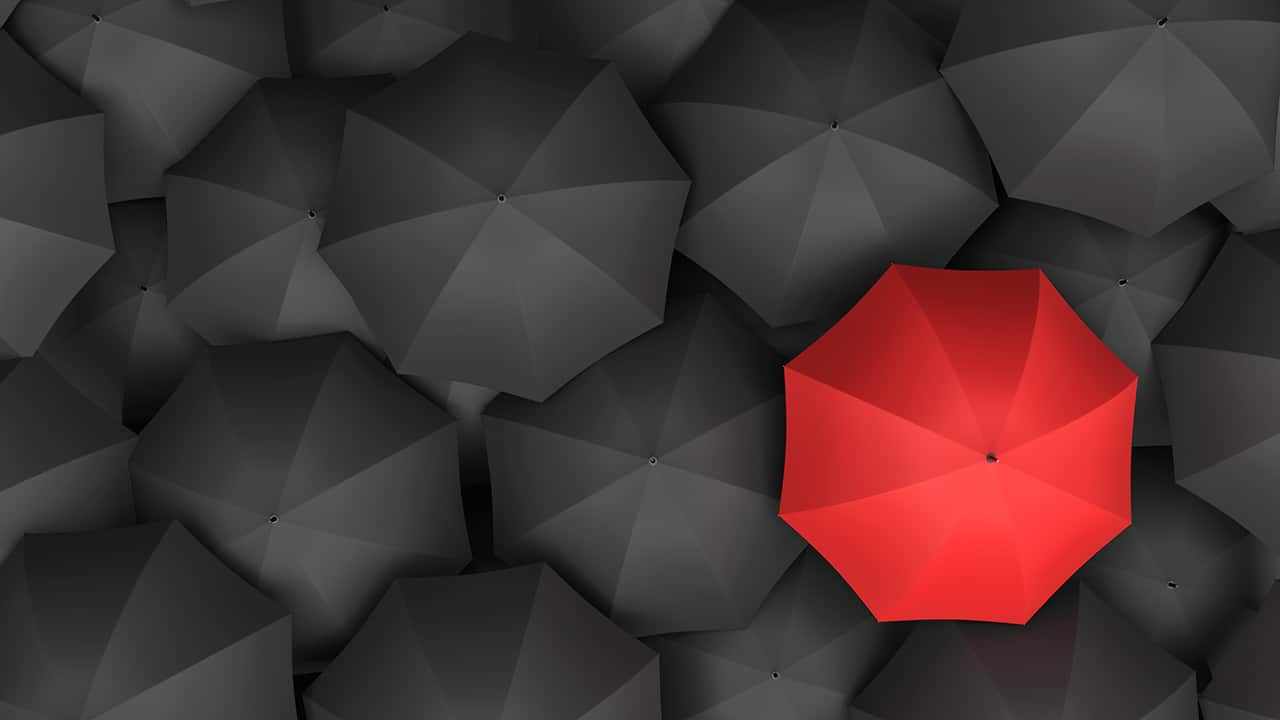 Picture: An inconsistent red umbrella in a sea of black umbrellas.