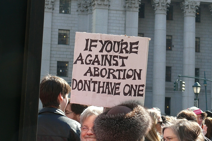 "Man holding sign with slogan, ""If you're against abortion, don't have one."""