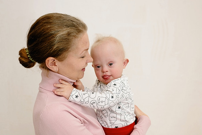 Mom holding baby with down syndrome